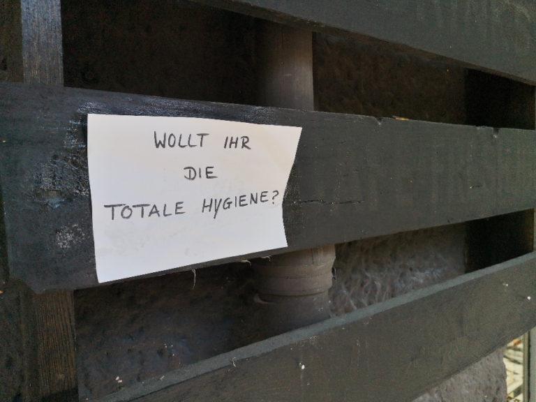 """Auf einer dunkel lasierten Holzpalette an einer Fassade hängt ein handschriftlicher Zettel mit der Aufschrift """"Wollt ihr die totale Hygiene?"""""""