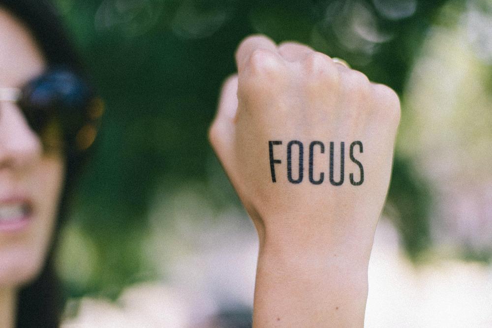 """Im hintergrund verschwommen das Profil einer Frau, im Vordergrund und Fokus ihre Faust. Auf dem Handrücken steht """"Focus""""."""