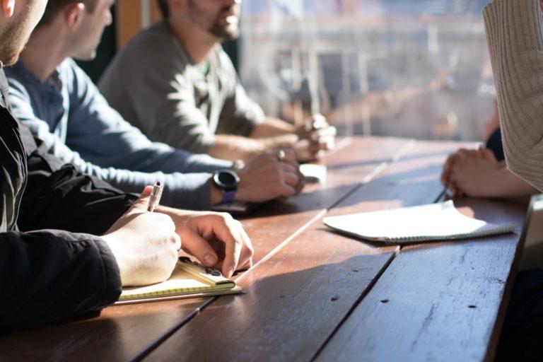 Menschen sitzen um Tisch, Man sieht nru ihre Hände.