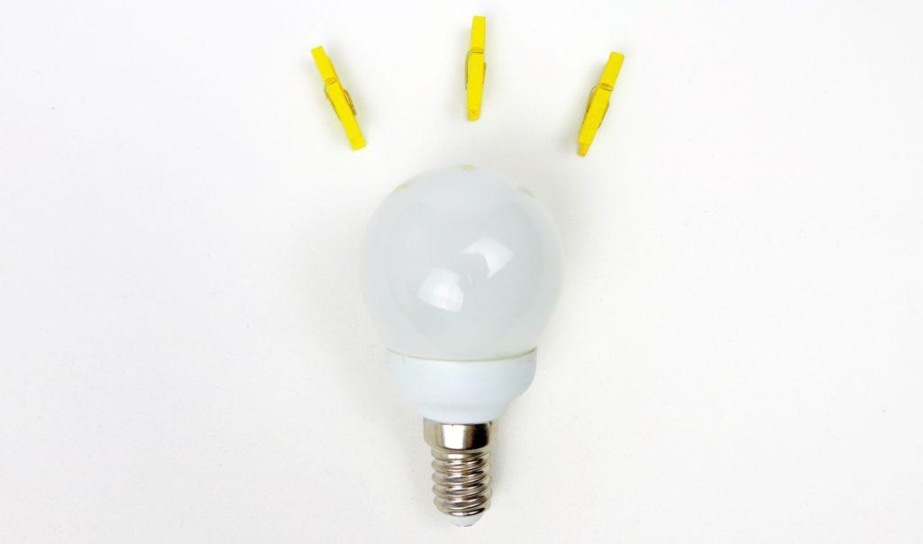 Glühbirne liegt vor weißem Untergrund. Über ihr befinden sich drei gelbe Steckklammern.