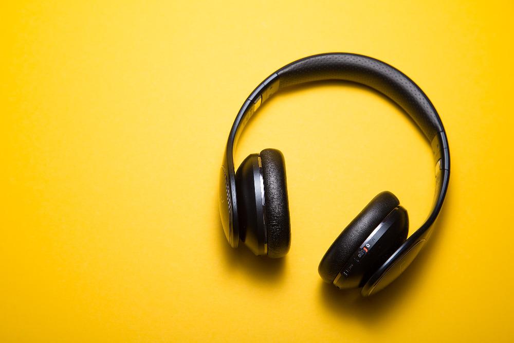 Schwarze Kopfhörer liegen auf gelbem Untergrund.