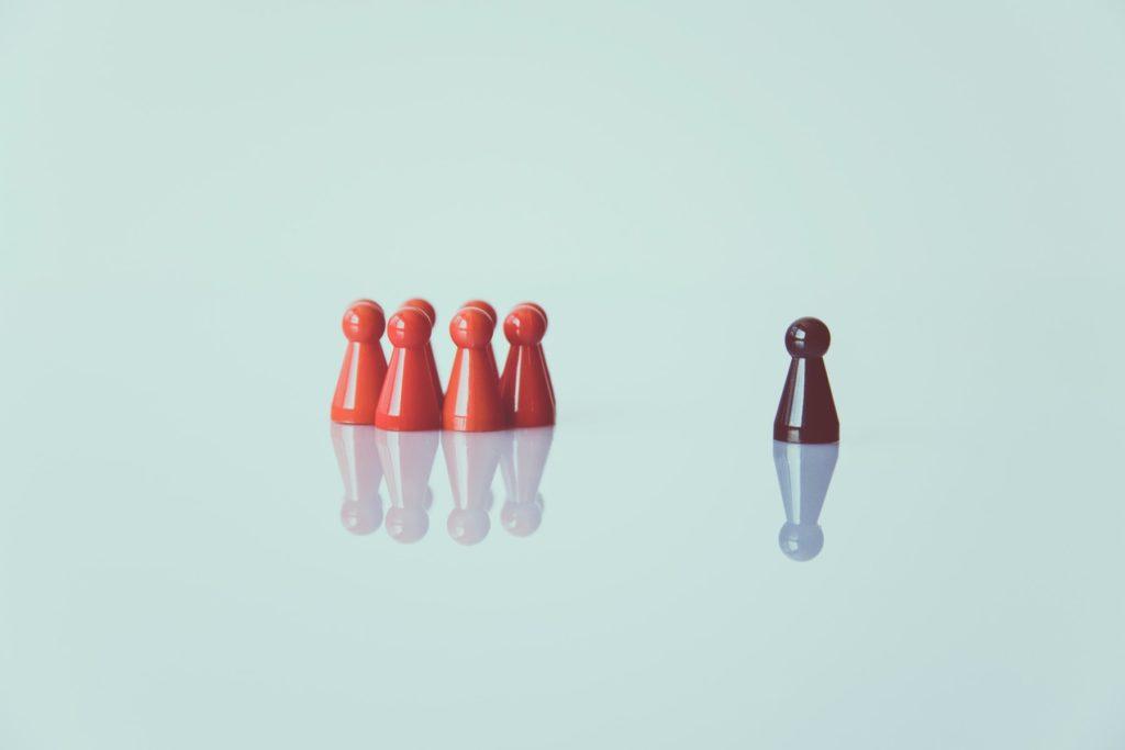 Rote Speilfiguren stehen eng beieinander. Daneben eine einzelne schwarze Spielfiguren, die alleine steht.