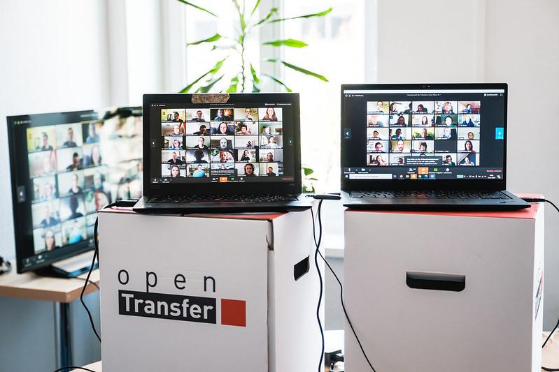 Zwei Laptops mit Kacheln eines vollen Zoom-Raums stehen auf Hockern von openTransfer. Im Hintergrund ein weiterer Monitor mit einem weiteren Zoom-Raum und eine Grünpflanze.