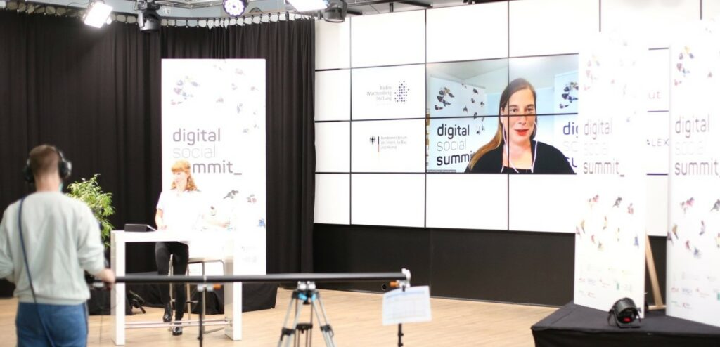 Teresa Sickert moderiert den Summit, vor ihr steht ein Kameramann, der sie aufnimmt.