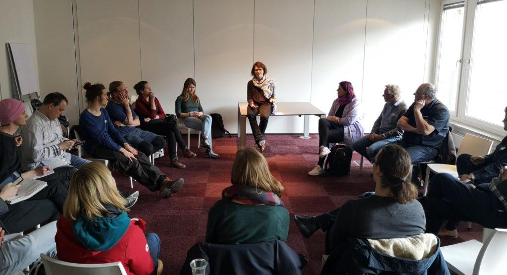 D3-Expeditionsteilnehmer;:innen sitzen im Stuhlkreis und hören Aline Blankertz zu