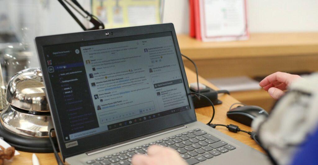 Ein Laptop schräg von der Seite fotografiert zeigt das Programm Slack.
