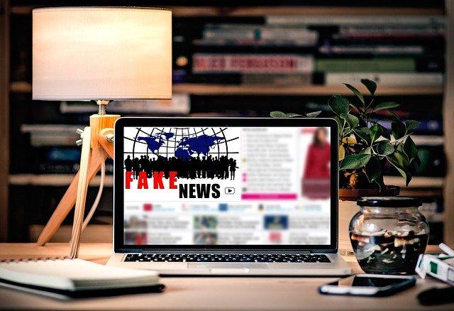 """Auf einem Schreibtisch steht ein Lapttop, auf dem eine Nachrichtenseite zu sehen ist, auf der """"Fake News"""" steht. drumhrum: Handy, Lampe, Bücherregal."""