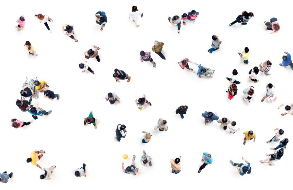 Foto aus Vogelperspektive auf Menschen, die vor weißem Boden in kleinen Grüppchen stehen