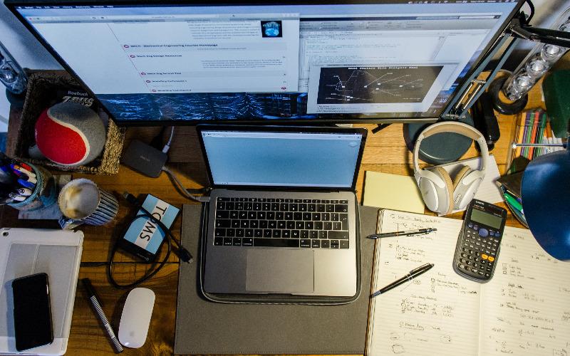 Vogelperspktive auf einen Schreibtisch mit einen großen Bildschirm voller offener Programme, davor ein Laptop. Drumherum liegt Zubehör: Taschenrechner, Stifte, Notizblock, Kopfhörer, Kabel, Stifte, Ball und Kaffeetasse.