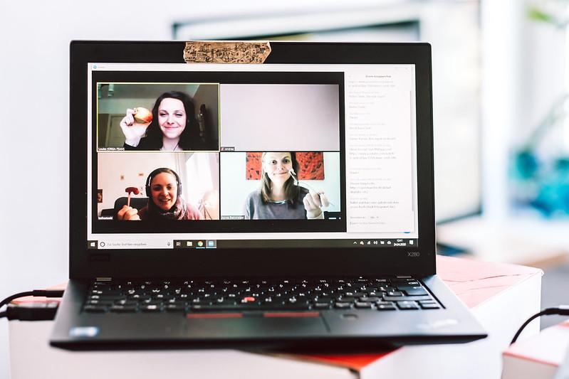 Drei Frauen sind in einem Videocall zu sehen, sie halten ihr Mittagessen in die Kamera.