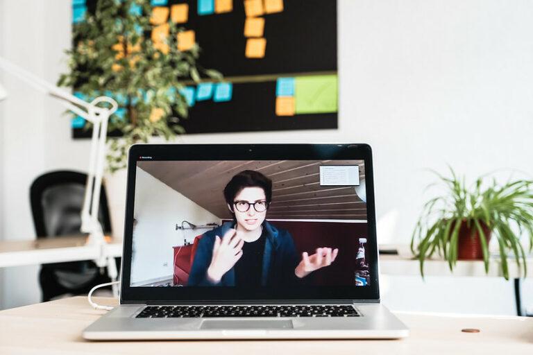 EIne Frau gestikuliert in einem Video, das auf einem Laptop abgespielt wird. Im Hintergrund sieht man ein Büro mit Pflanze und einem schwarzen Board voller Postits.