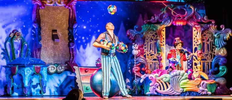 Auf einer magisch bunten und vollen Bühne jongliert ein Mann mit mehreren Bällen.