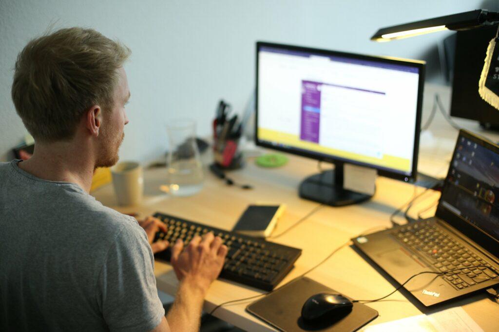 Foto zeigt einen jungen Mann im Halbprofil, der vor einem Laptop und einem zweiten Bildschirm im Schein einer Schreibtischlampe arbeitet.