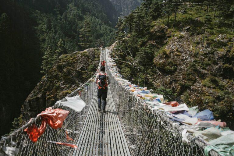 Ein Mann geht über ine mit Tüten behängte lange Hängebrücke mitten in der Natur, vermutlich China.