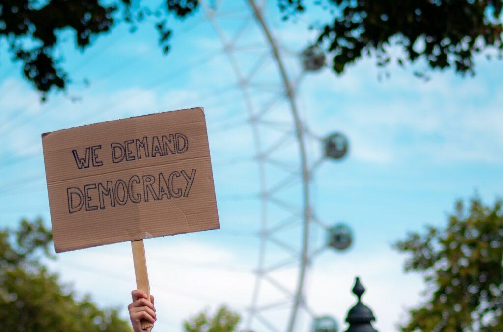 """Ein Protestschild, auf dem """"We demand democracy"""" steht, wird hochgehalten."""