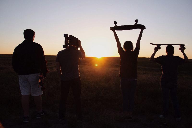 Vier Jugendliche sind als Silhouetten gegen das Abendlicht zu erkennen, sie tragen Skateboards auf ihren Schultern bzw. über dem Kopf und laufen über ein Feld.