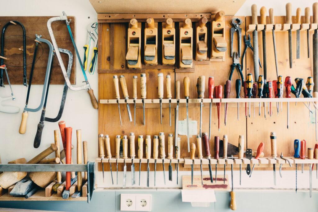 EIne volle hölzern Werkzeugbank mit vielen Hobeln, Spateln und mehr in Holz, an der Seite hängen Sägen.