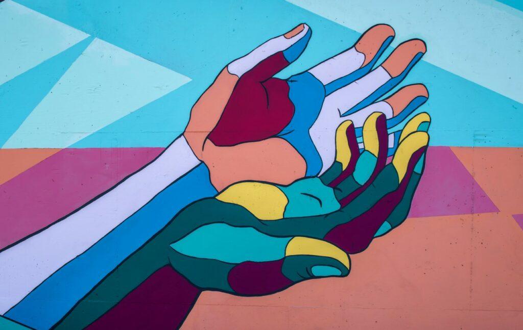 Streetart. Zwei farbige Hände umfassen sich.