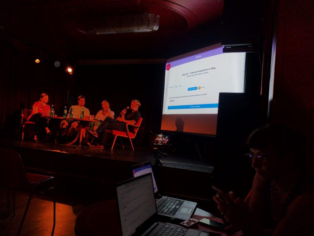 Man sieht eine dunkle Bühne, im Hintergrund eine Leinwand, auf der das Tool Interaktive Veranstaltung eingeblendet ist. Vorn in der Ecke sieht man enschen an Laptops.