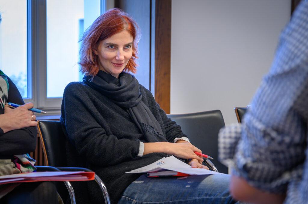 Susann Reissig mit kinnlangem roten Haar, grauem Pulli und Schal schaut in die Kamera.