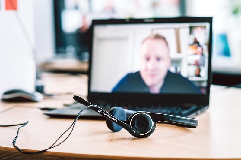 Auf einem Schreibtisch liegt ein Headset. Dahinter erkennt man verschwommen einen Laptop mit Videocall mit einer Person in Großaufnahme und weiteren Personen in Miniaturansicht.
