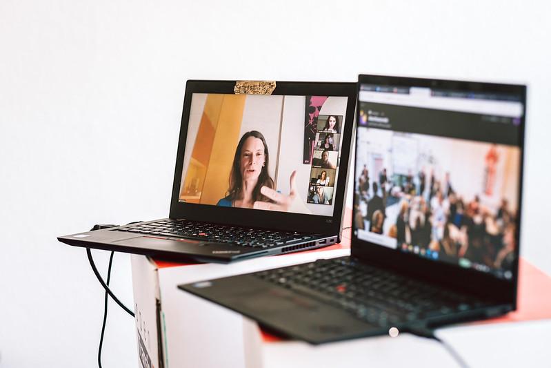 Zwei Laptops stehen nebeneinander. Auf einem gestikuliert eine Frau, auf dem anderen sieht man eine Gruppe Menschen