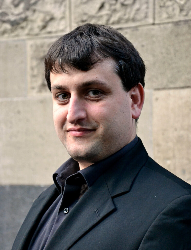 Lorenz Overbeck schaut vor einer grauen Wand in die Kamera, er trägt einen dunklen Anzug