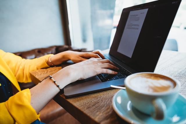 Man sieht Hände auf einer Tastatur eines Laptops, in dem ein Textdokument geöffnet ist. daneben auf dem Tisch steht eine Tasse Kaffee oder Cappuccino.