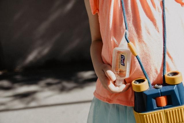 Man sieht den Oberkörper eines Erwachsenen in einem lachsfarbenen Shirt. Vor der Brust baumelt ein Fernglas. An seiner Schnur klemmt ein kleines Fläschen Handdesinfektionsmittel