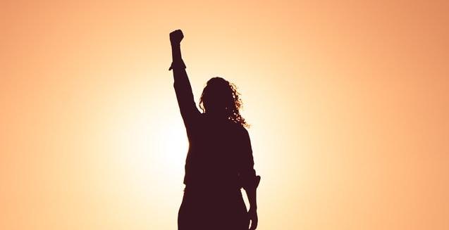 Im orangefarbigem Gegenlicht steht die Silhouette einer Person mit langen Haaren, die Hand zur Siegesfaust geballt.