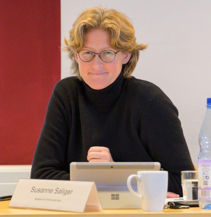 Susanne Saliger sitzt an einem Tisch mit Namensschild, Kaffeetasse und strahlt in die Kamera.