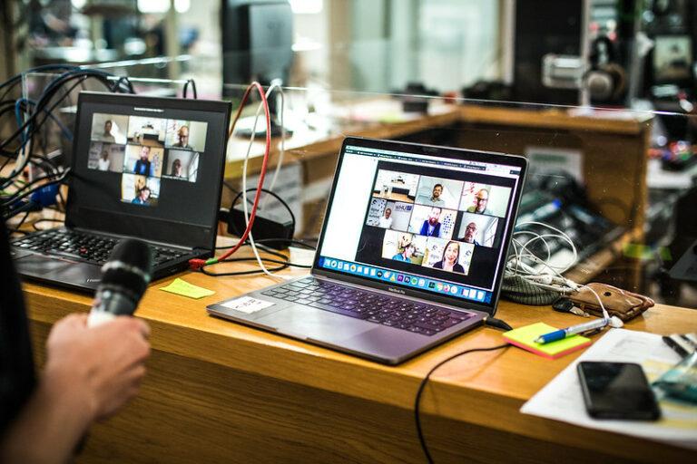 Zwei Laptops stehen auf einer Theke, auf beiden läuft ein Zoom-Call, drumherum Kabel, Mikros und Studioatmoshäre