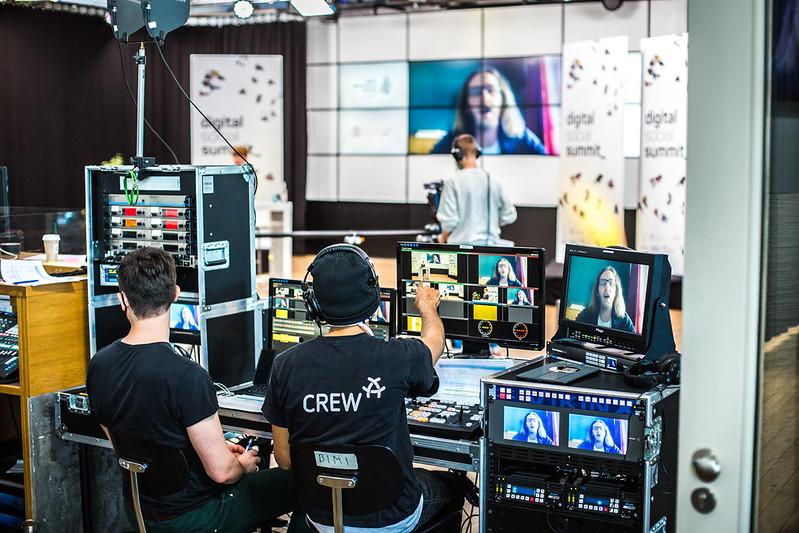 Zwei Männer sitzen an einem Mischpult für Bild und Ton, im Hintergrund sieht man einen Kameramann, der die Moderatorin vor einer Leinwand filmt, auf der wiederum ein digital zugeschalteter Interviewpartner zu sehen ist.