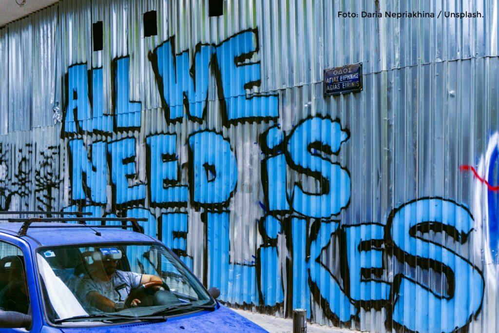 """Foto eines Graffiti mit Text """"All we need is likes""""."""