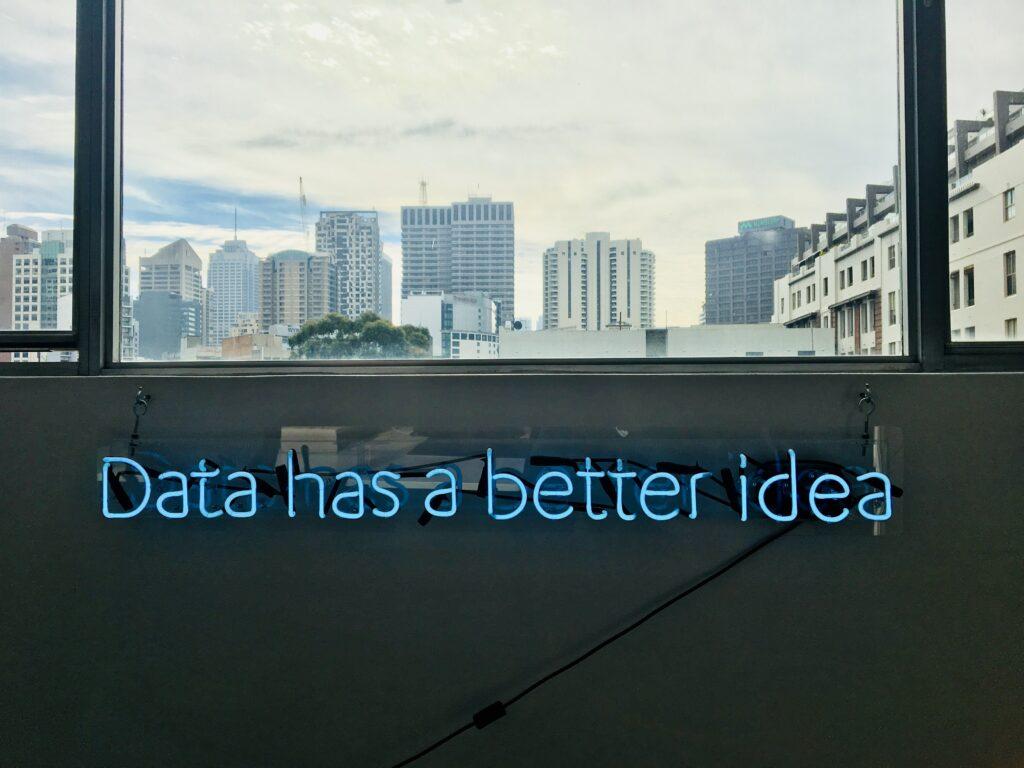 """Unter einem Fenster, das die Skyline einer Großstadt zeigt, steht in blauen Leuchtbuchstaben """"Data has a better idea""""."""