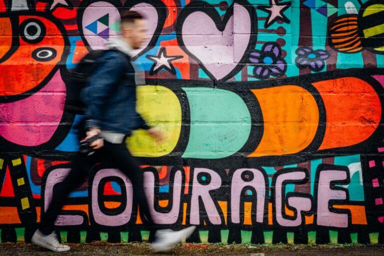 """Man läuft vor einer Wand lang auf der ein Graffiti mit dem Text """"Courage"""" steht."""