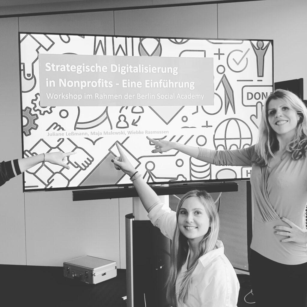 """Wiebke Rasmussen und eine Kollegin stehen neben einer Leinwand auf der steht """"Stategische Digitalisierung in Nonprofits"""". Sie ziegen auf ihre Namen, die unter dem Titel stehen und lächeln in die Kamera. Das Bild ist schwarz-weiss."""