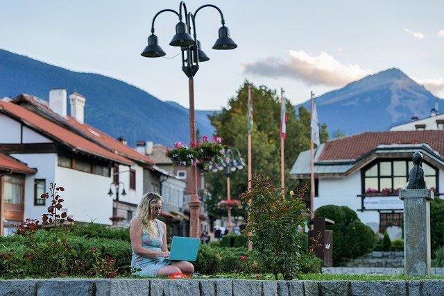 Ein Dorfplatz, im Hintergrund Berge, auf einer Mauer sitzt eine Frau am Laptop.