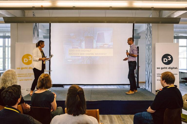 Friedemann Schnur und Insa Heinemann stehen auf der Bühne des D3 Community Events 2020. Im Hintergrund die Präsentation ihrer Digitalstrategie