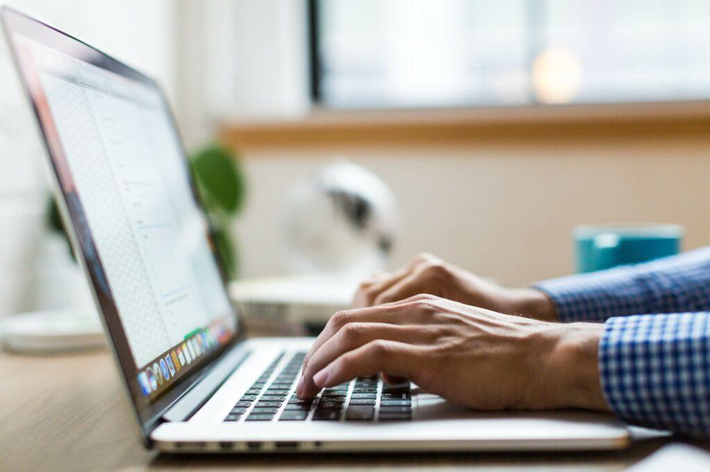 Foto eines Laptops auf desssen Tastatur zwei Hände sind, die tippen.