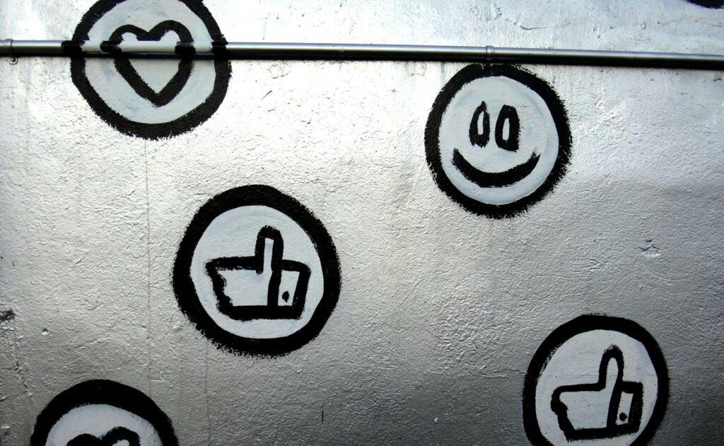Foto von einer Wand auf der umkreiste Herzen, Smileys und Daumen-hoch-Symbole, mit schwarzem Edding gemalt sind.