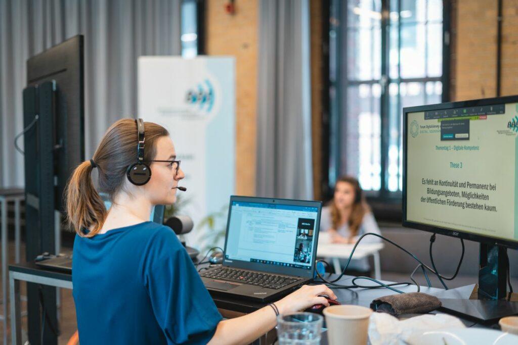 Über die Schulter einer jungen Frau an zwei Regie-Laptops sieht man im Hintergrund eine Moderatorin beim BBE-Forum Digitalisierung und Engagement