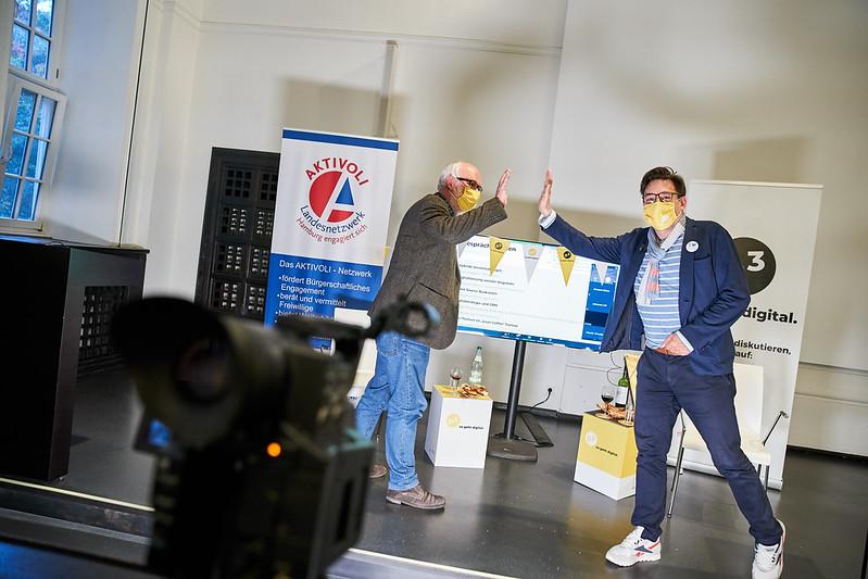 Auf der Bühne des D3-Community Events sieht man Tom Leppert und Tomislav Perisic, wie sie, einen gelben D3-Mund-Nasenschutz tragen, sich fast ein High-Five geben - ihre Hände stoppen kurz voreinander.