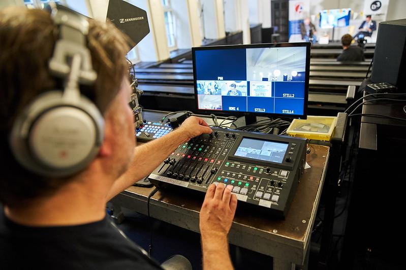 EIn Technik-Mischpult mit Display und vielen Reglern sowie ein Mann mit Kopfhlrern, der es bedient. Im Hintergrund verschwommen Tom Leppert und Tomislav Perisic, die das D3-COmmunity Event live aus Hamburg moderieren.