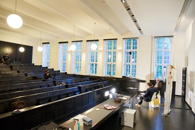 Man sieht den Hörsaal im Museum für Hamburgische Geschichte, aus dem heraus das D3-Community-Event Teil 1 gestreamt wurde. Vorne sieht man die beiden Moderatoren, ins Auge stechen die leeren Sitzbänke im zukünftigen Haus des Engagements.