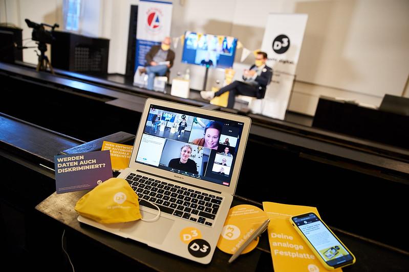 Im Vordergrund sieht man das D3-Team in einem Zoom-Call auf kleinen Kacheln auf einem Bildschirm. Der Laptop steht am oberen Rand eines Hörsaals, um ihn drapiert D3-Masken, Notizbücher und Sticker in gelb. Unten im Hörsaal sieht man verschwommen die Moderatoren Tom Leppert und Tomislav Perisic vor den Rollups von Aktivoli und D3 - so geht digital.