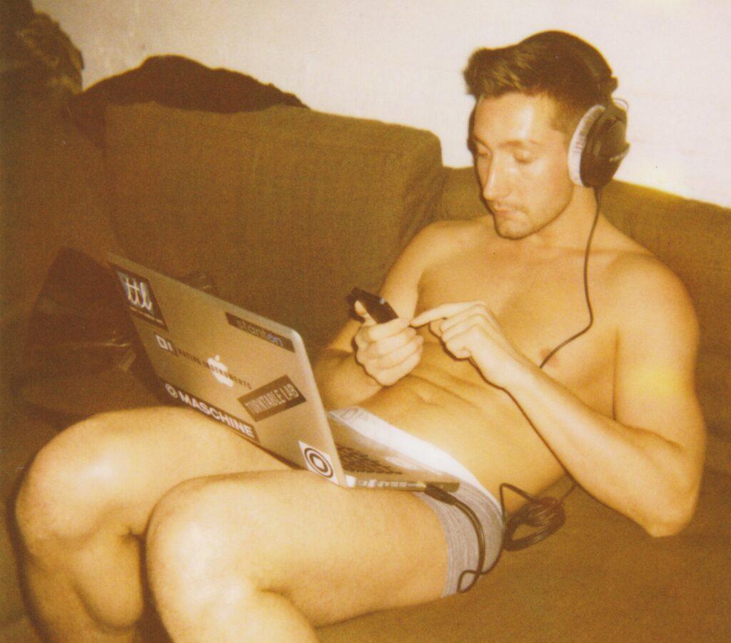 Foto eines jungen Mannes in Boxershorts mit Laptop auf seinem Schoss, der auf sein Smartphone tippt.