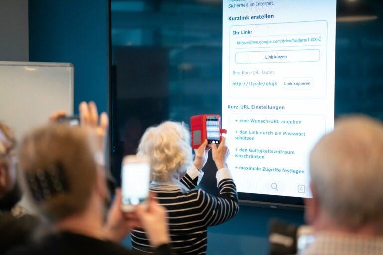 Foto von Senior:innen, die in einem Seminarraum einen Google-Link abfotografieren.
