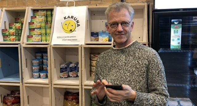 Foto von Jorg Richert im Karuna-Store mit Smartphone in der Hand.