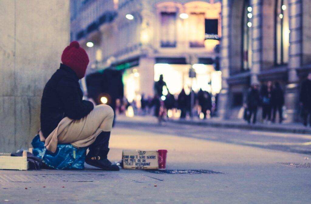 Foto eines Obdachlosen, der auf einer Einkaufsstrasse auf dem Boden sitzt.